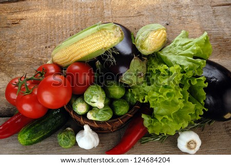 Composition with vegetables in wicker basket on wooden board