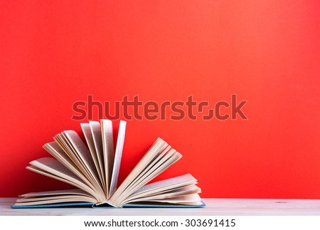 Composition with vintage old hardback books, diary, fanned pages on wooden deck table and red background. Books stacking. Back to school. Copy Space. Education background.