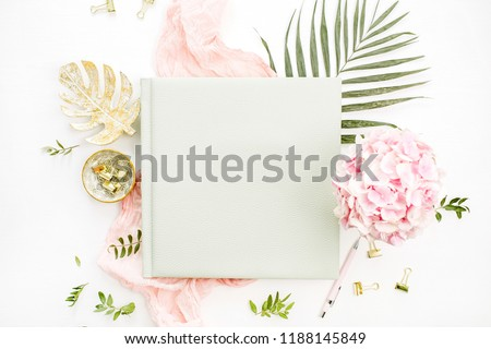Composition with wedding or family photo album, hydrangea flower bouquet, tropical palm leaf, pastel pink blanket, gold monstera plate on white background. Flat lay, top view still life concept.