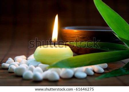 Composition with white zen stones, burning candle, bamboo leaves and clay bowl with tea symbolizing harmony, calmness and relaxation