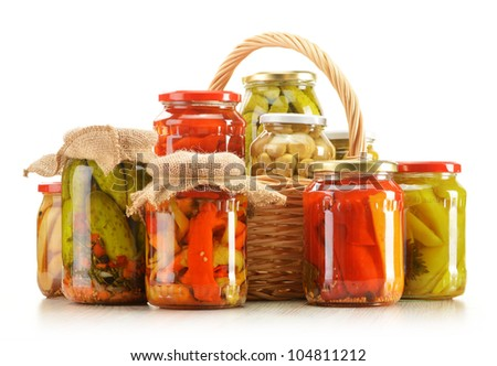 Composition with wicker basket and jars of pickled vegetables. Marinated food. - stock photo