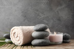 Composition with zen stones, towel and candle on table against grey background
