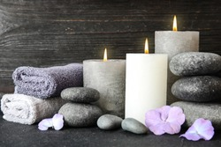 Composition with zen stones, towels and candles on table against wooden background