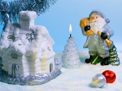 Compositions with Santa Claus, fabulous house and candle.