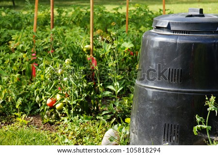 Compost bin made of recycled plastic next to beautiful vegetable garden with ripe tomatoes. Recycling, green, concept.