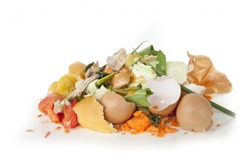 Composting pile of rotting kitchen fruits and vegetable scraps as a banana peel orange and onion garbage waste for recycling as an environmentally responsible compost that enriches soil in a garden.