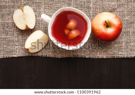 Compote stewed fruit drink with sliced apple on burlap cloth background with copy space.