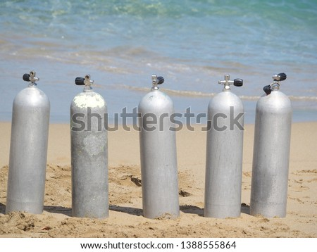compressed air cylinders for diving by the ocean. #1388555864