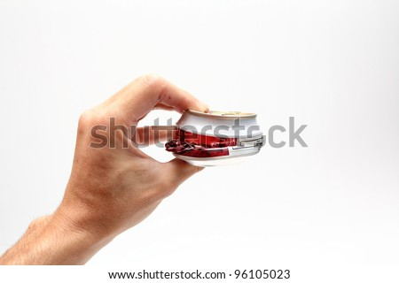 Compressed beer can in hand - stock photo