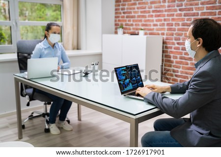 Computer Analyst Working On Laptop Wearing Face Mask