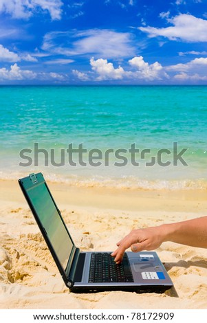 Computer and hand on beach, business travel background