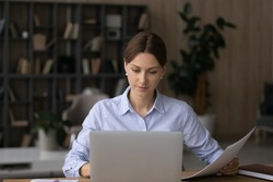 Computer and papers. Focused millennial woman office worker teacher freelancer do paperwork manage legal documents fill in electronic form. Young lady lawyer study text of contract agreement by laptop
