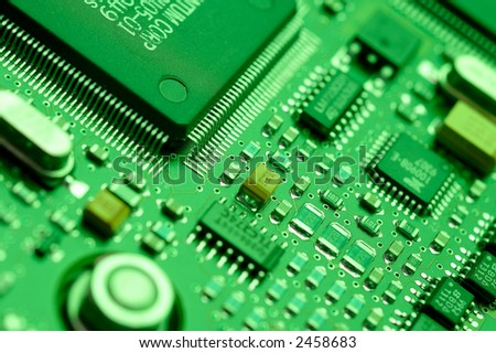 Computer chips on a circuit board with green lighting