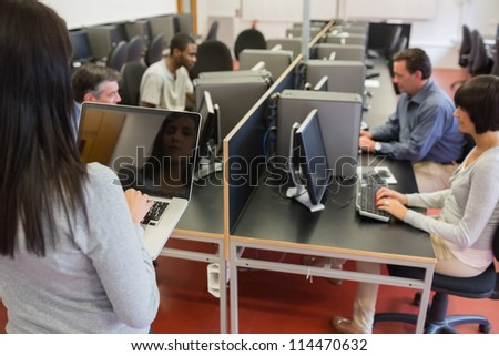 Computer class working as teacher is typing on laptop in college