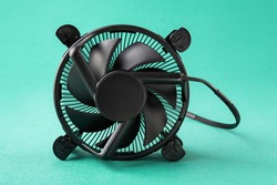 Computer CPU cooling fan radiator on its side over a turquoise blue green textured background. Desktop maintenance and repair. Modern PC hardware components and equipment. Front view.
