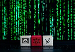 Computer cyber hacker concept with wooden blocks and malware, virus and black hat hacking icons - State sponsored security terrorism warfare attack with lines of ransomware code on laptop screen