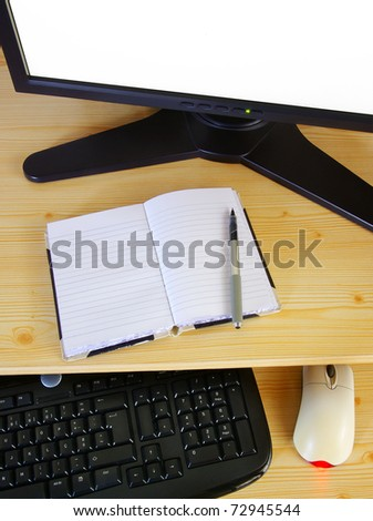 Computer desk with monitor, keyboard, mouse and an opened notebook and pen - stock photo