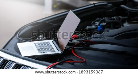 Computer diagnostics of the car in garage. Automotive mechanical technician using laptop computer programming and investing by car diagnostic software, car maintenance service concept.