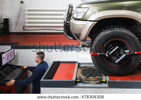 Computer diagnostics of wheel alignment for SUV at service. Professional car maintenance, modern technologies