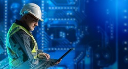 Computer engineering concept. Engineer is working on development computer systems. Engineer with laptop in hands. Work in field of computer engineering. Blurred technology background in background