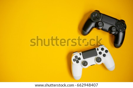Computer game competition. Gaming concept. White and black joysticks on yellow background.