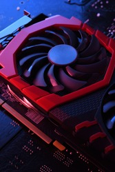 Computer game graphics card, videocard with two coolers on circuit board ,motherboard background. Close-up. With red-blue a lighting.