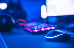 Computer gamer workplace for new game mouse and keyboard with blur pink neon light background.
