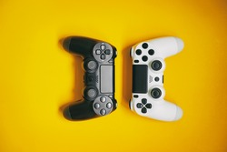 Computer gaming competition. Gaming concept. White and black joystick on yellow background.