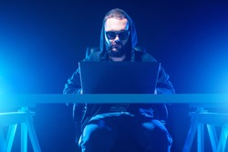 Computer genius. Computer geek with a hood works until late. Computer geek in a dark room. Guy with laptop illuminates blue light. geek man in sunglasses and a hood. Man with a laptop sits at a table
