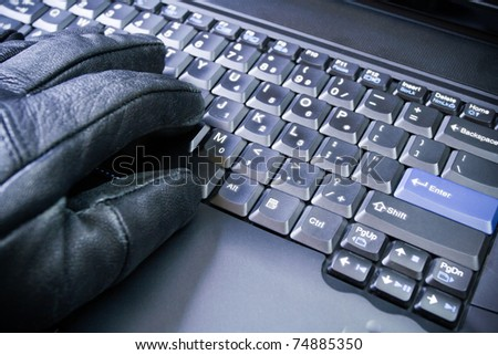 Computer hacker hand in glove working on laptop, dirty business