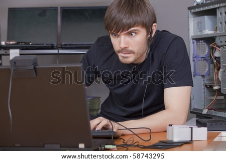 computer hacker in black shirt working at laptops