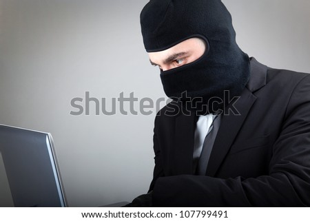 Computer hacker in suit and tie over grey background