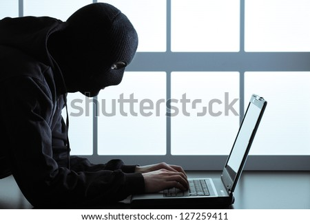 Computer hacker - Male thief stealing data from laptop