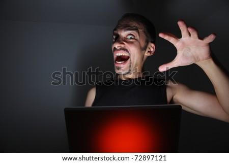 Computer hacker with laptop in dark room.