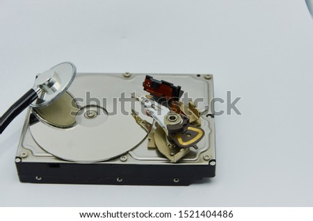Computer hard drive and a stethoscope. Components for PC. Open hard disk storage. Recovery and storage of information. Magnetic disks inside HDD. Modern digital technology. #1521404486