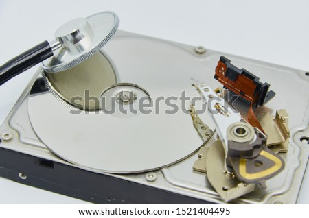 Computer hard drive and a stethoscope. Components for PC. Open hard disk storage. Recovery and storage of information. Magnetic disks inside HDD. Modern digital technology. #1521404495