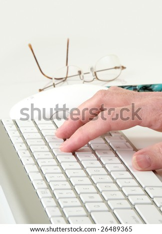 Computer keyboard and mouse with typing hand, eyeglasses, and pen