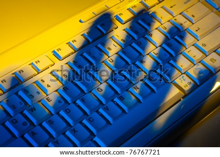 Computer keyboard and the shadow of a hand. Theft of data.