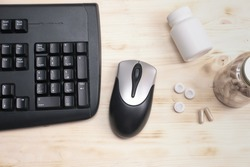computer keyboard, mouse and bottles of mental support supplement capsules. chewing gum for neuro boost. vitamins and l-theanine for nootropic effect. e-sport and gaming enhancers.