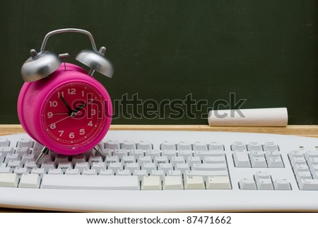 Computer keyboard on a desk with an alarm clock in front of a chalkboard with copy space, Time to get an education online