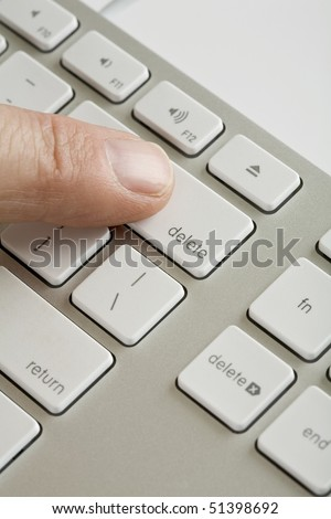 Computer keyboard with mans finger on delete key