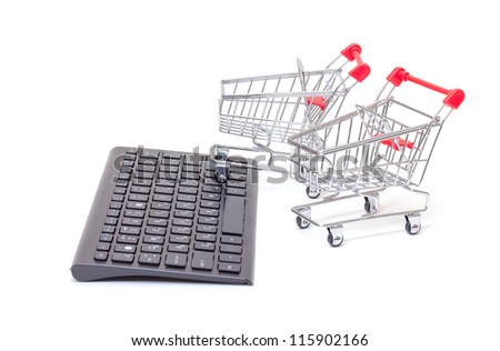 Computer keyboard with two miniature wire shopping carts conceptual of online retail sales and purchases isolated on white