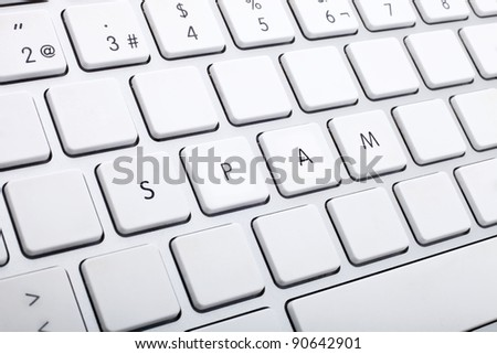 Computer keyboard with white keys forming the word spam
