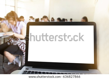 computer,laptop screen with blank space for text on Blurry front view of college people taking exams in class room on seat rows in a classroom educational institute background.