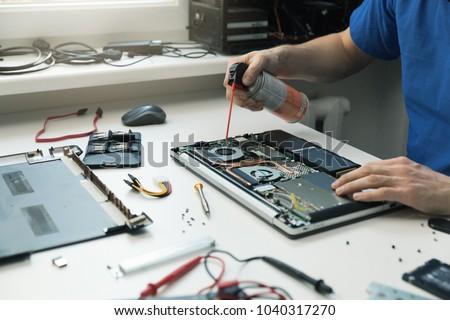 computer maintenance - technician blow out dust from laptop fan #1040317270