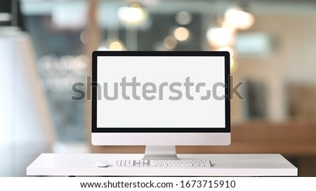 Computer monitor with white blank screen putting on white working desk with wireless mouse and keyboard over blurred vintage office as background.