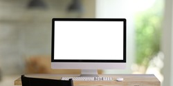 Computer monitor with white blank screen putting on workspace wooden desk with keyboard and mouse over blurred living room as background.