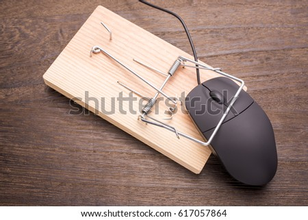 Computer mouse caught by the mousetrap device on wooden table #617057864