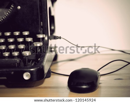Computer mouse connected to vintage typewriter