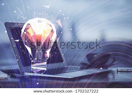Photo of  Computer on desktop in office with bulb icon hologram. Multi exposure. Concept of idea.